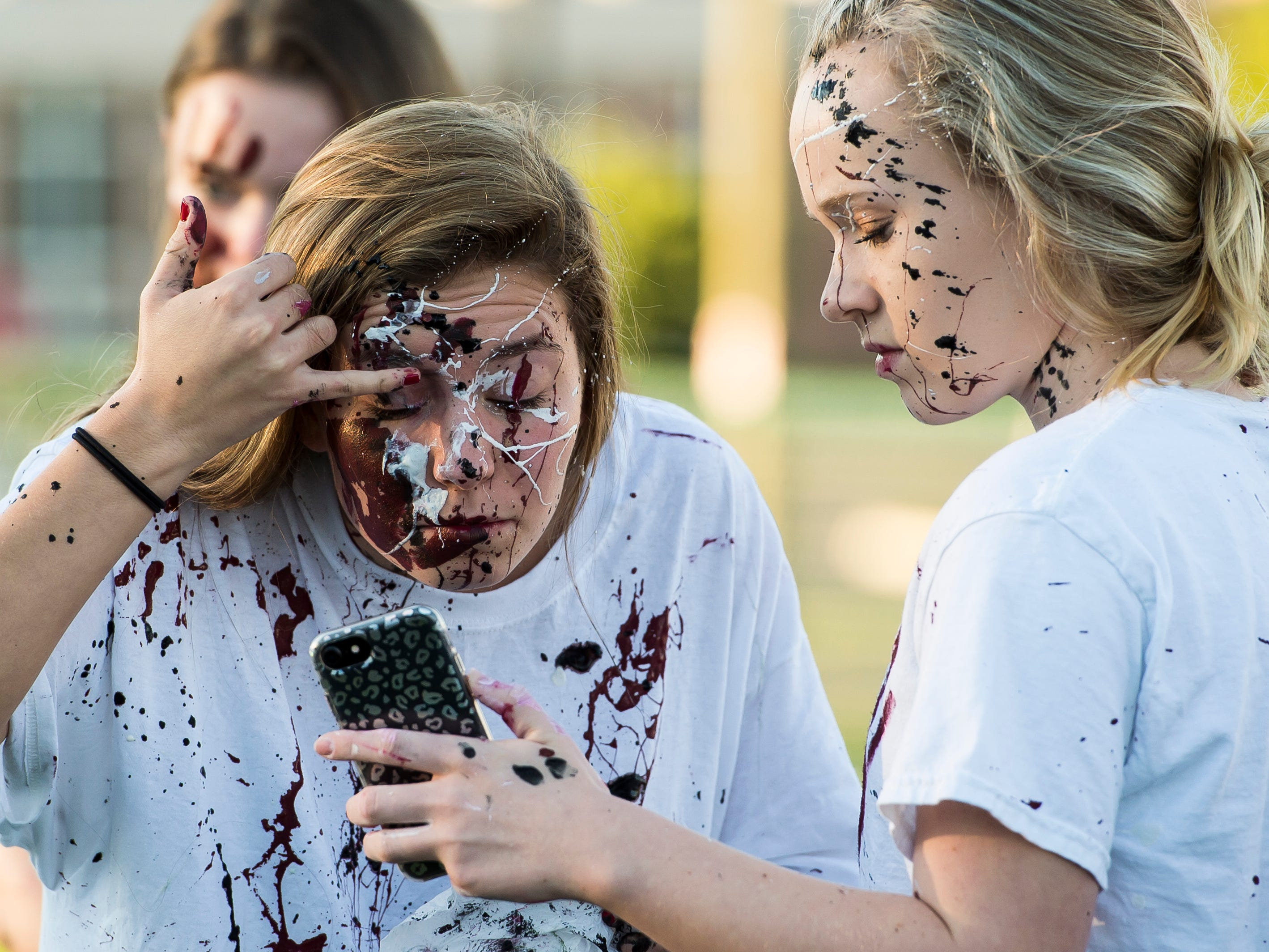 """A Gettysburg student checks the paint on her face during a """"splatter-fest"""" prior to the football game against Eastern York on Friday, September 28, 2018. The fest helped raise money for the school's Mini-THON."""