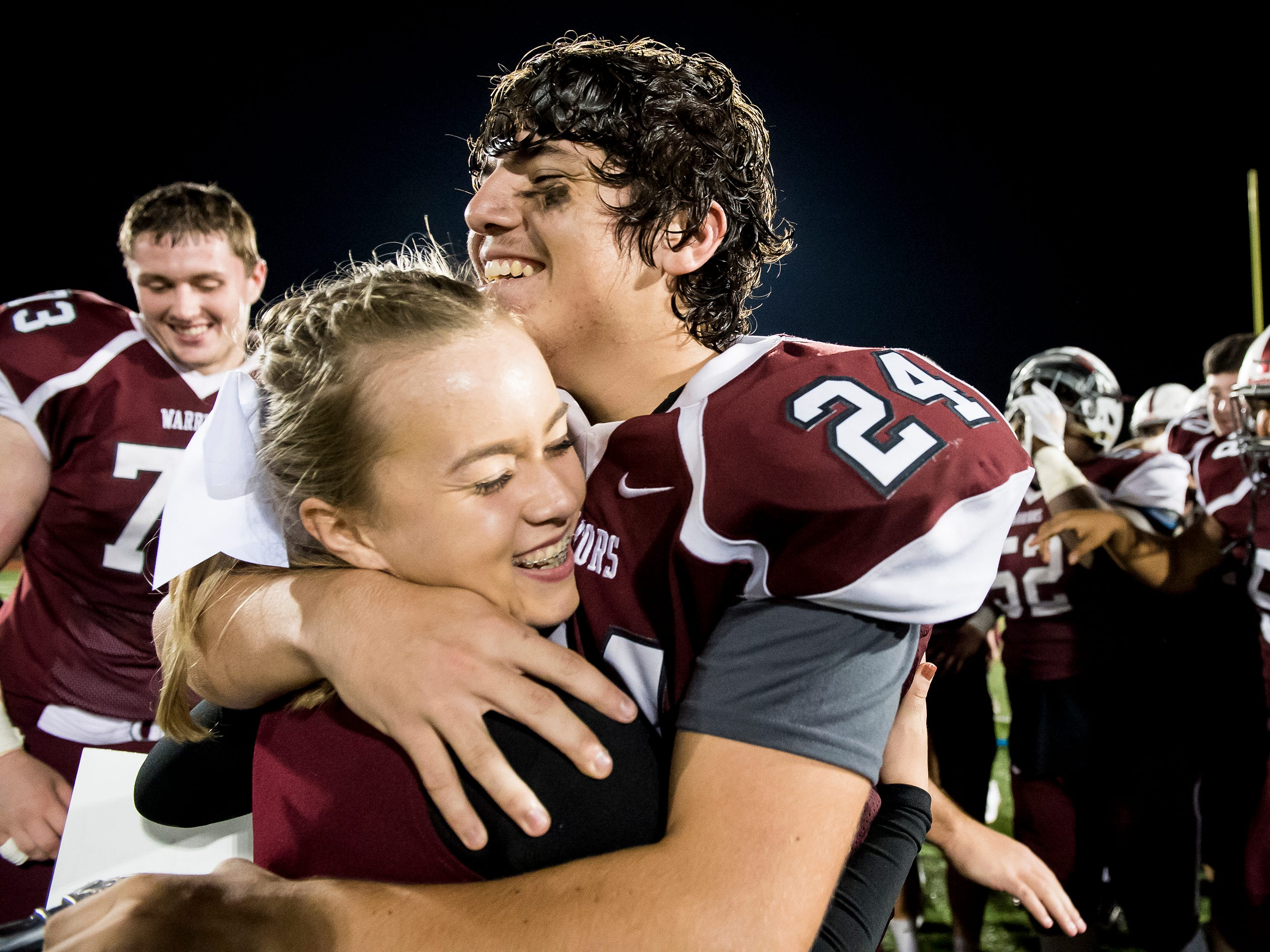 Gettysburg football player Alvaro Sanchez embraces his girlfriend, Veronica Yingling, after she surprised him with a homecoming proposal follwing a game against Eastern York on September 28, 2018.
