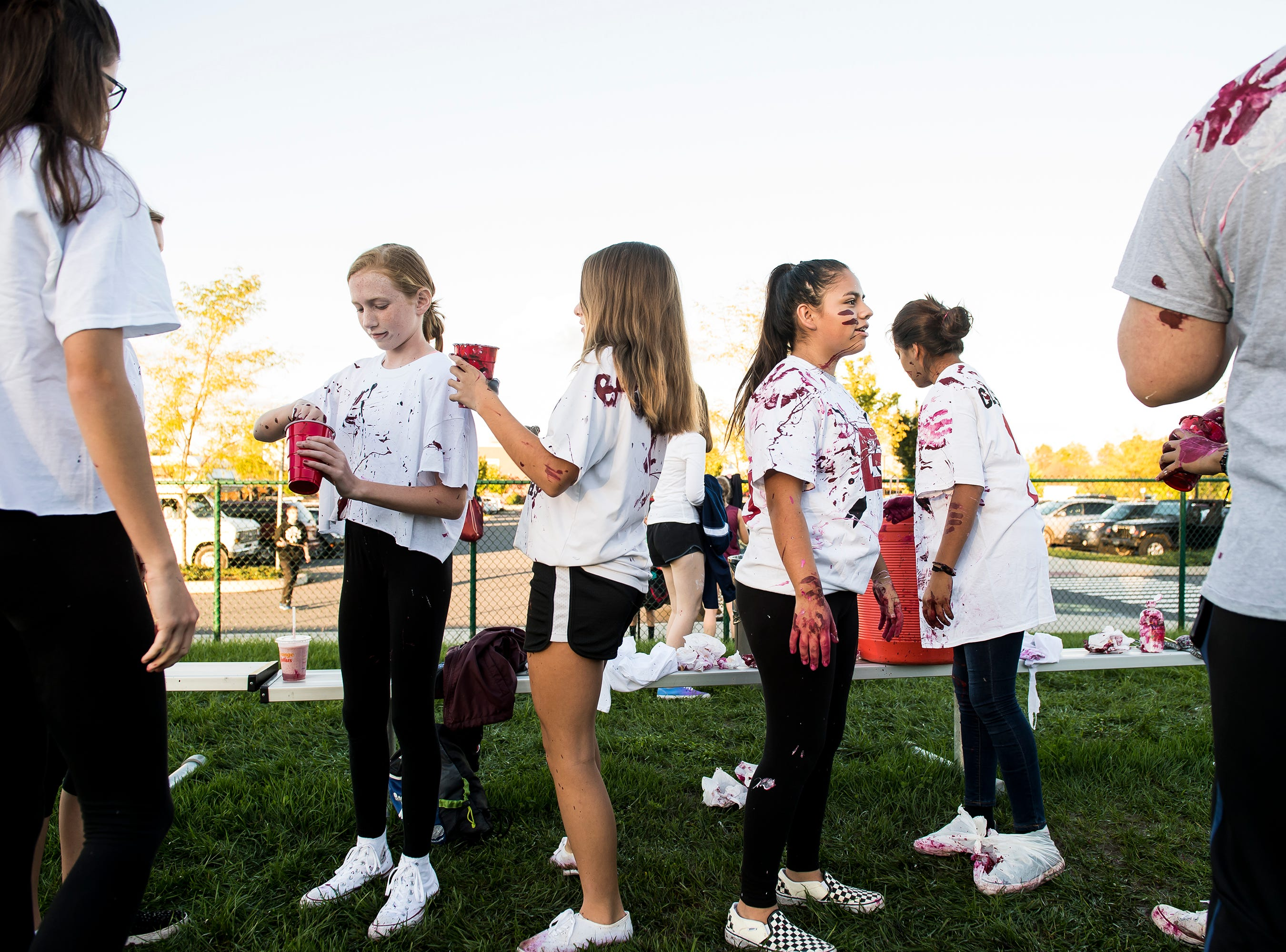 """Gettysburg students cover each other in paint during a """"splatter-fest"""" prior to the football game against Eastern York on Friday, September 28, 2018. The fest helped raise money for the school's Mini-THON."""