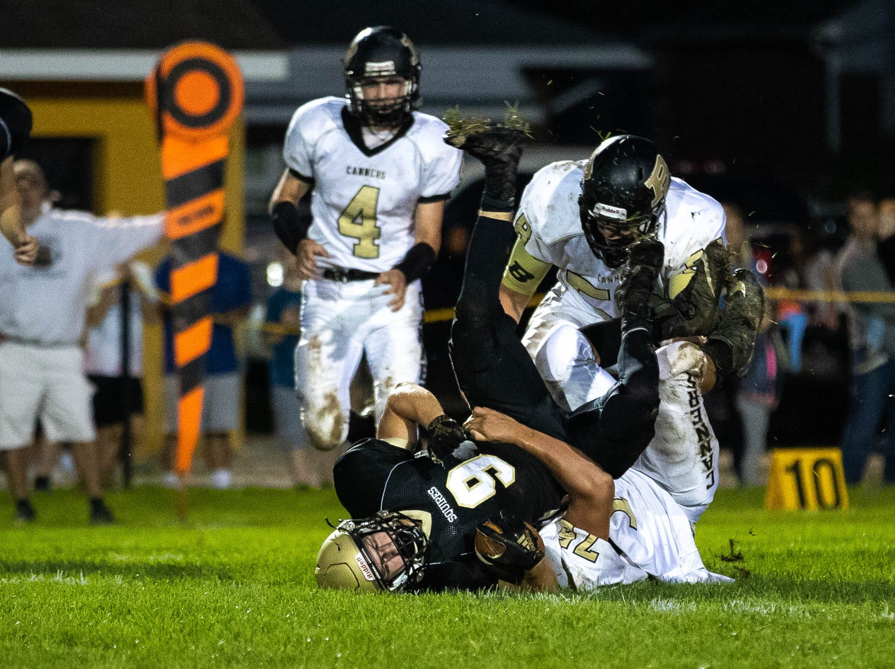 Delone's Logan Brown (9) is flipped upsidedown while tackled by Biglerville's Derek Tosten (15) during the first half of a football game between Delone Catholic and Biglerville, Friday, Sept. 28, 2018, in McSherrystown. Delone led Biglerville 35-0 at the half.