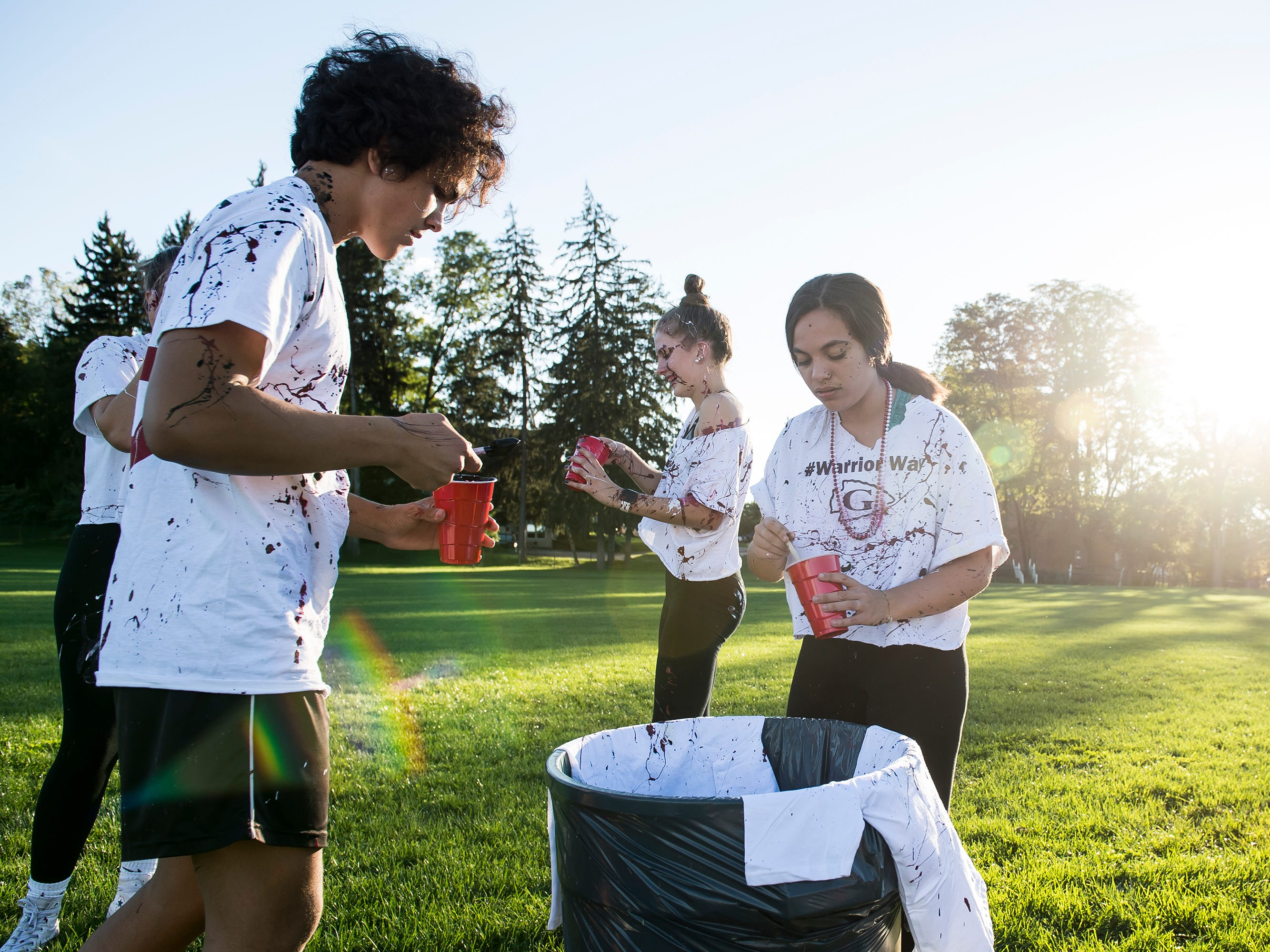 """Gettysburg students cover a shirt in paint during a """"splatter-fest"""" prior to the football game against Eastern York on Friday, September 28, 2018. The fest helped raise money for the school's Mini-THON."""