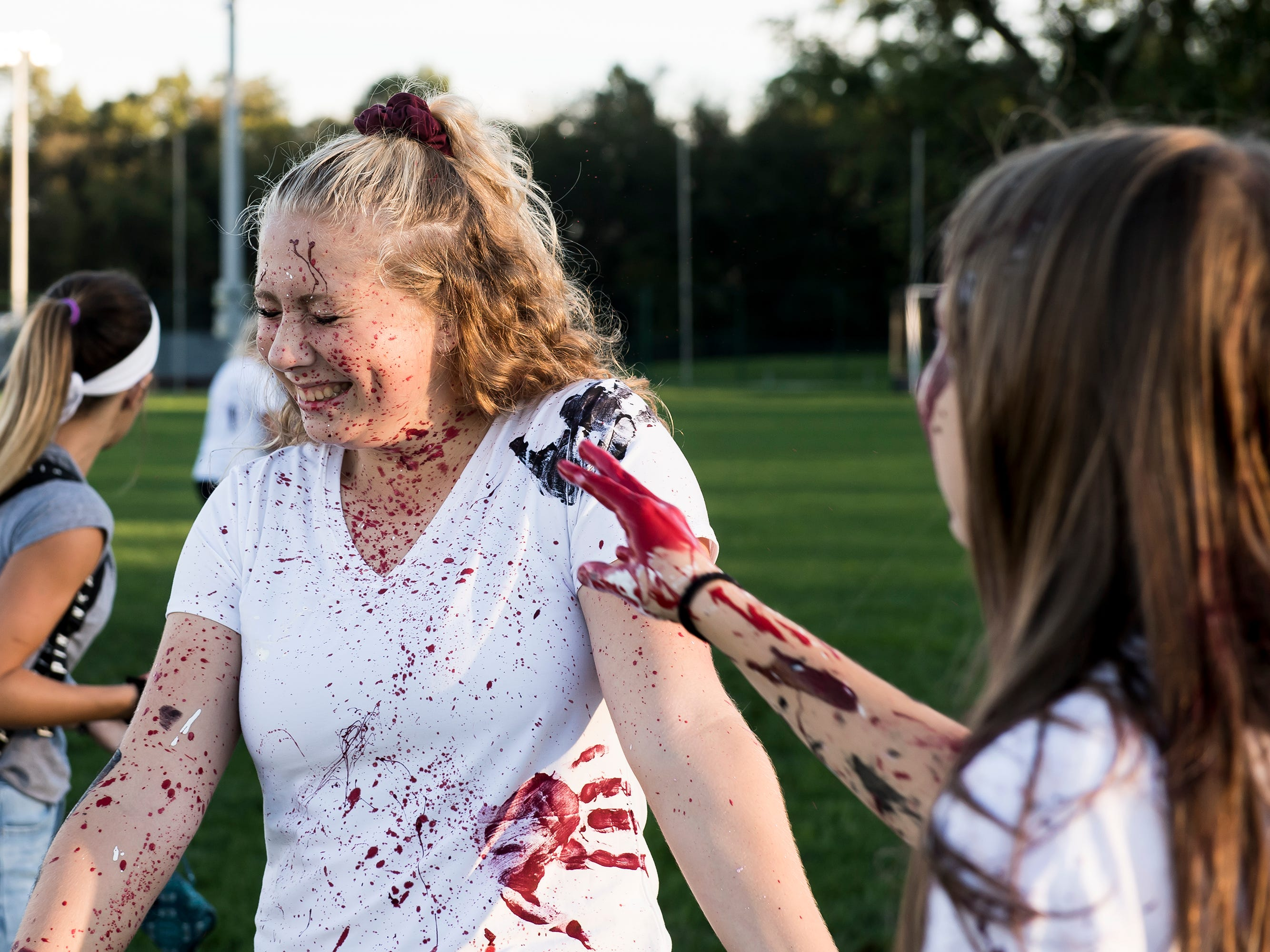 """A Gettysburg student gets covered in paint during a """"splatter-fest"""" prior to the football game against Eastern York on Friday, September 28, 2018. The fest helped raise money for the school's Mini-THON."""