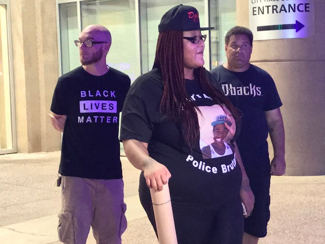 A woman condemns police brutality near Phoenix City Hall on Friday evening.
