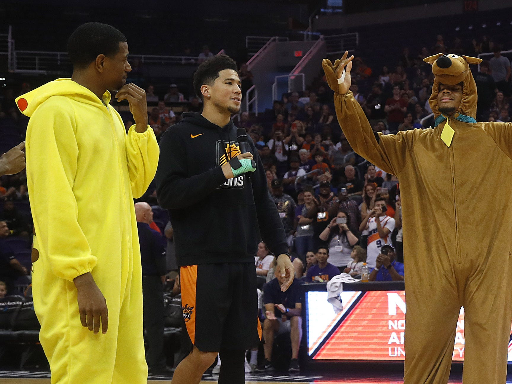 Suns Devin Booker has fans vote between De'Anthony Melton in a pikachu costume and Elie Okobo in a Scooby Doo costume after a dance-off during an Open Practice at Talking Stick Resort Arena in Phoenix, Ariz. on Sept. 29, 2018.