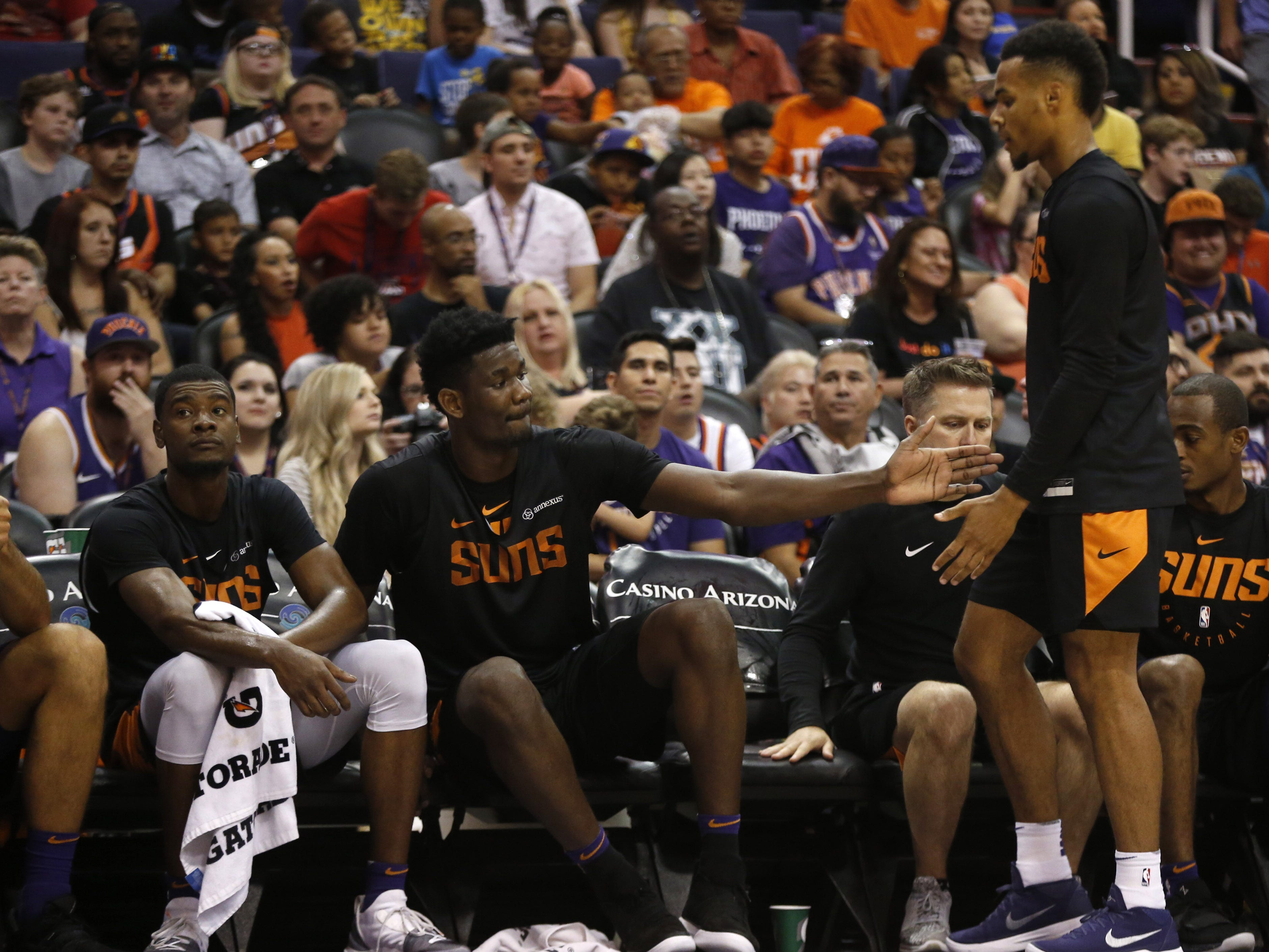Suns Deandre Ayton high-fives Ellie Okobo on court during an Open Practice at Talking Stick Resort Arena in Phoenix, Ariz. on Sept. 29, 2018.