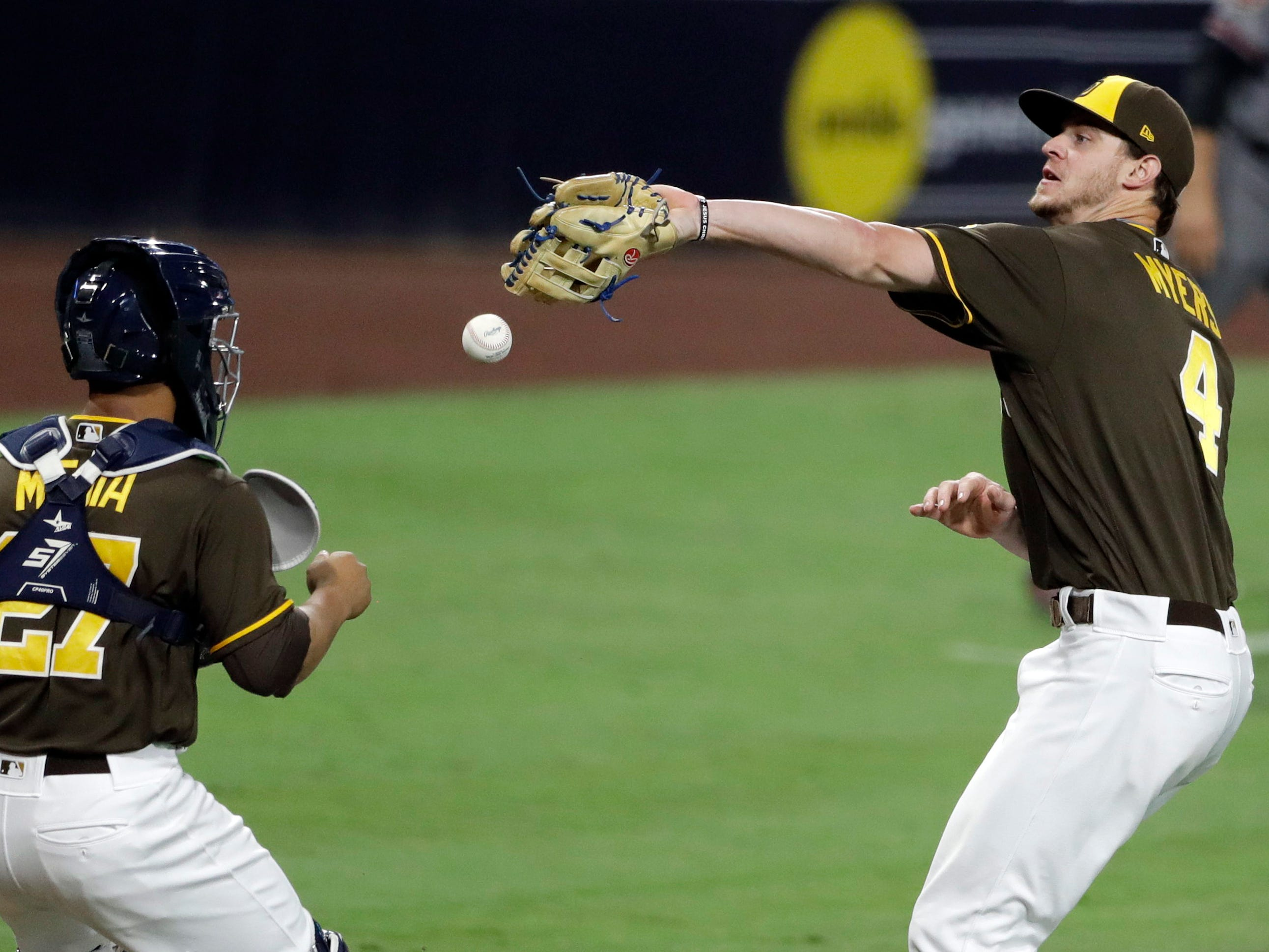 San Diego Padres third baseman Wil Myers, right, misses the catch on a pop bunt by Arizona Diamondbacks' Patrick Corbin as catcher Francisco Mejia (27) watches during the second inning of a baseball game Friday, Sept. 28, 2018, in San Diego. A runner was forced at third, and Corbin was safe.