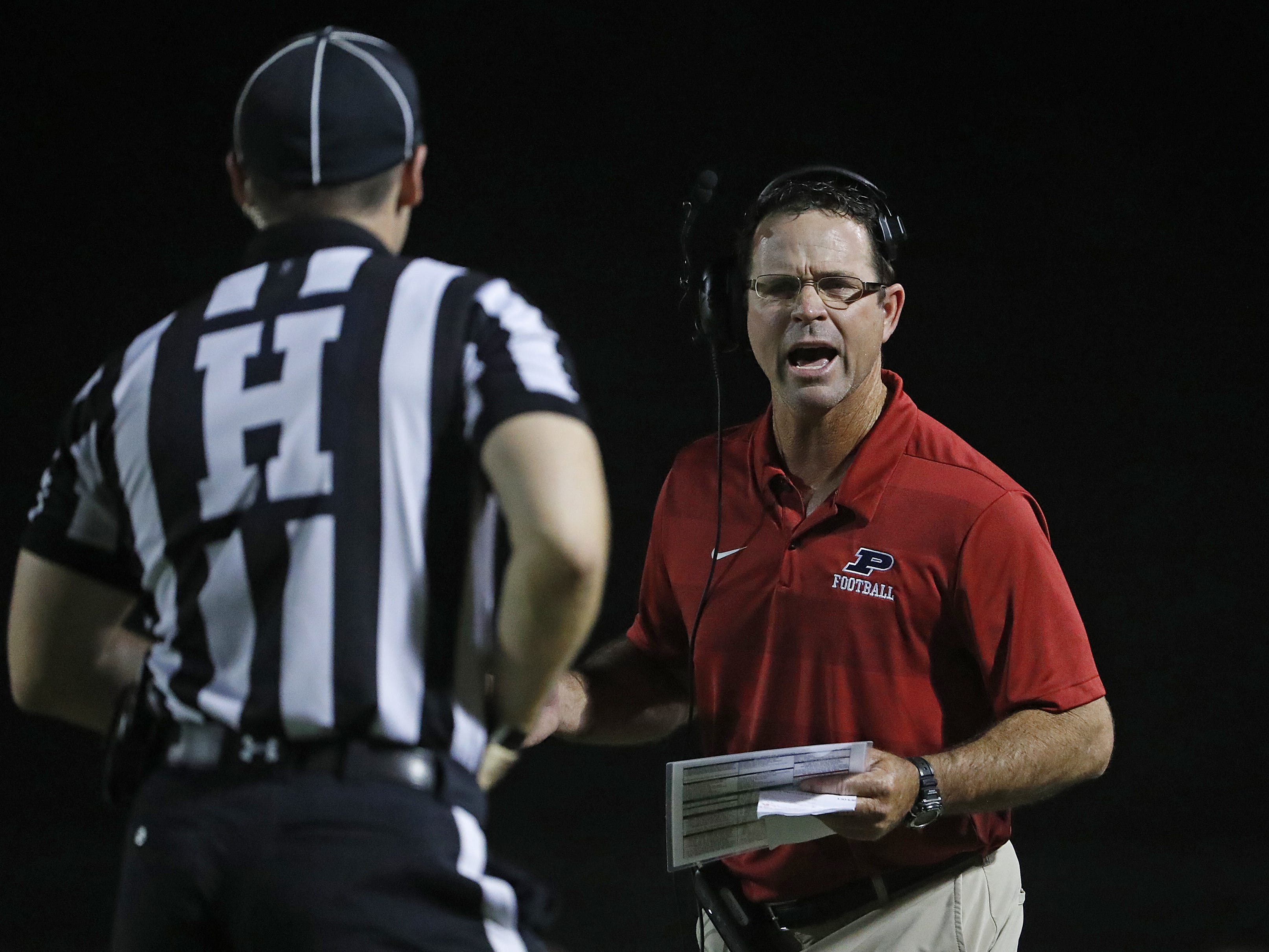 Perry's head coach Preston Jones argues with an official over a false start penalty against Chandler at Perry High School in Gilbert, Ariz. on Sept. 28, 2018.  #azhsfb
