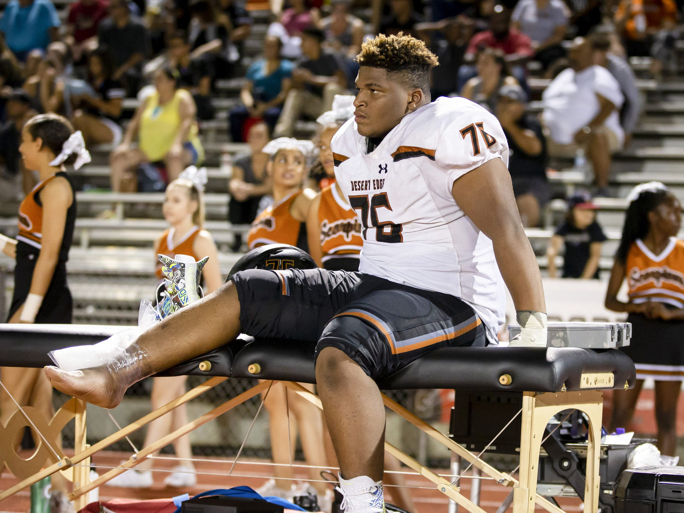 Freshman defensive tackle Isaiah Williams (76) of the Desert Edge Scorpions ices his ankle on the sidelines during the game against the Saguaro Sabercats at Saguaro High School on Friday, September 28, 2018 in Scottsdale, Arizona. #azhsfb