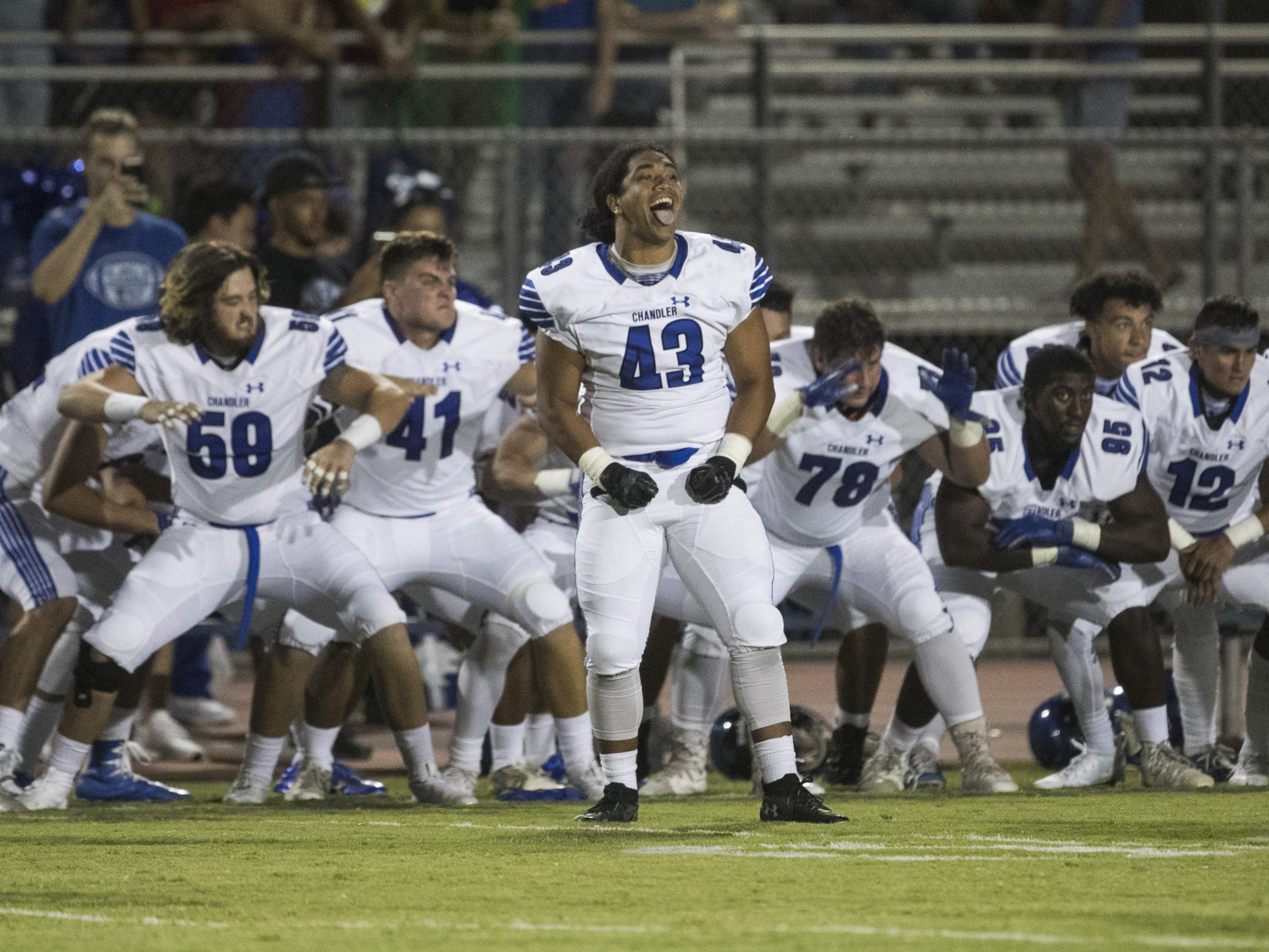 Chandler's Javan Ah Quin (43) sticks out his tongue as the team performs a 'hake' dance before a game at Perry High School in Gilbert, Ariz. on Sept. 28, 2018.  #azhsfb