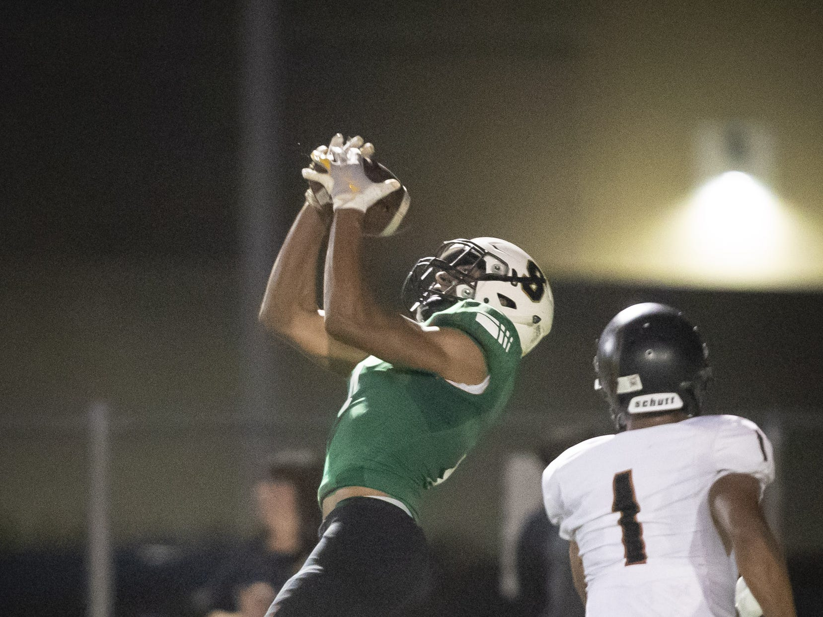 Junior wide receiver Matt Polk (4) of the Saguaro Sabercats catches a reception against sophomore free safety Steven Ortiz (1) of the Desert Edge Scorpions at Saguaro High School on Friday, September 28, 2018 in Scottsdale, Arizona. #azhsfb
