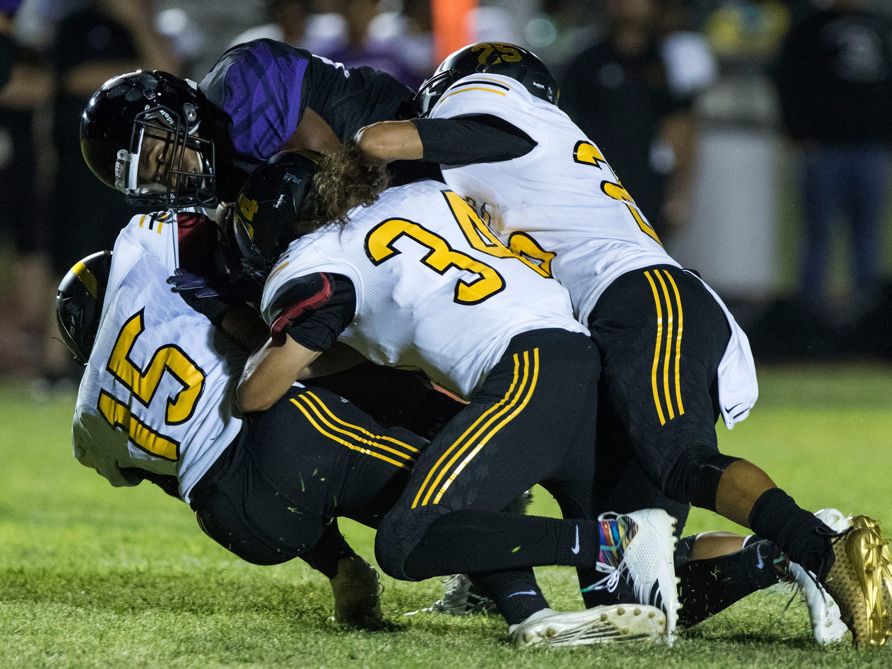 Millennium's Isaac Oliver gets gang tackled by Goldwater's defense during their game in Goodyear Friday, Sept. 28, 2018. #azhsfb