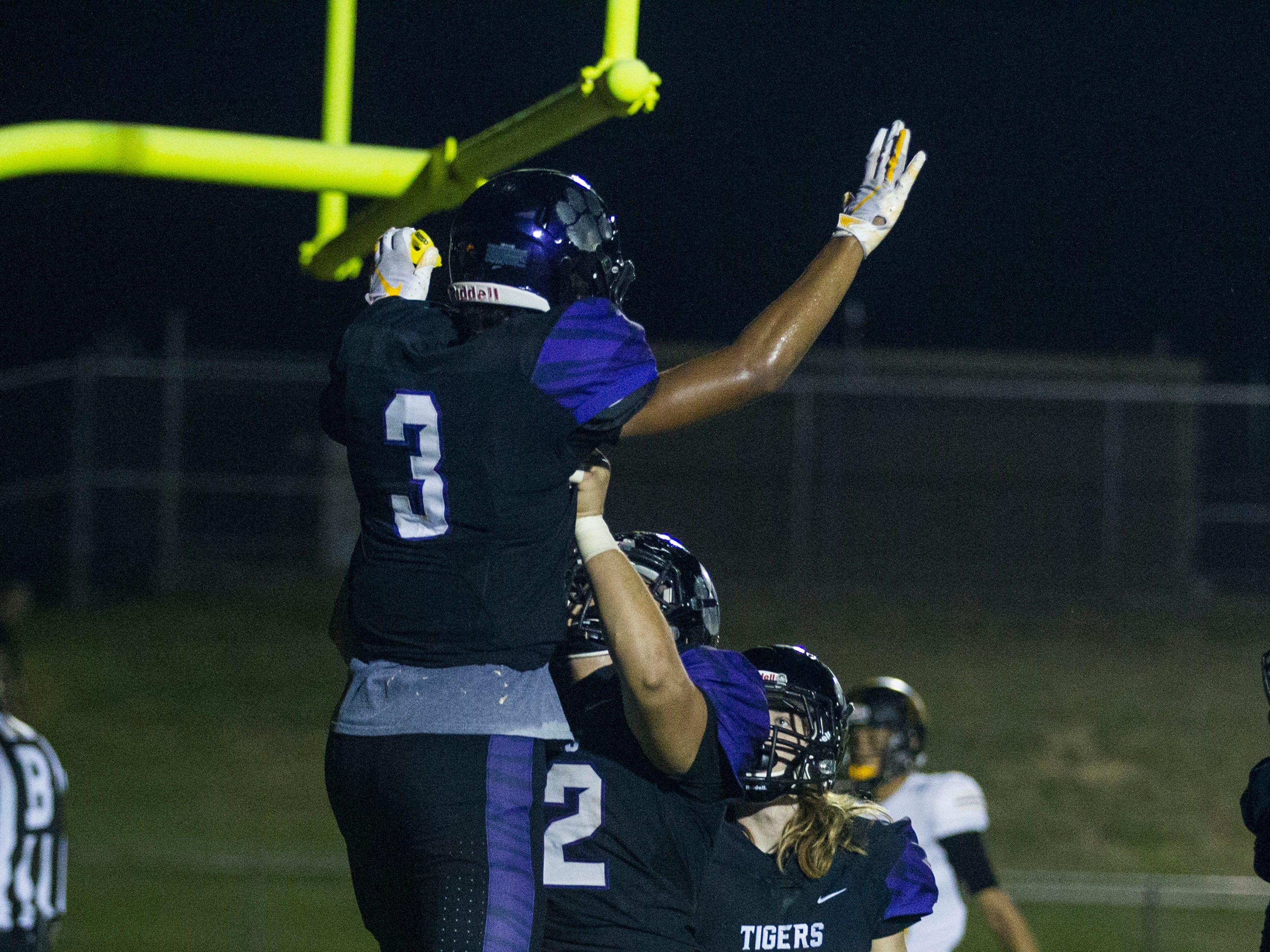 Millennium's Jaelon Taylor gets lifted in the air by teammate Jalan Early after scoring against Goldwater during their game in Goodyear Friday, Sept. 28, 2018. #azhsfb
