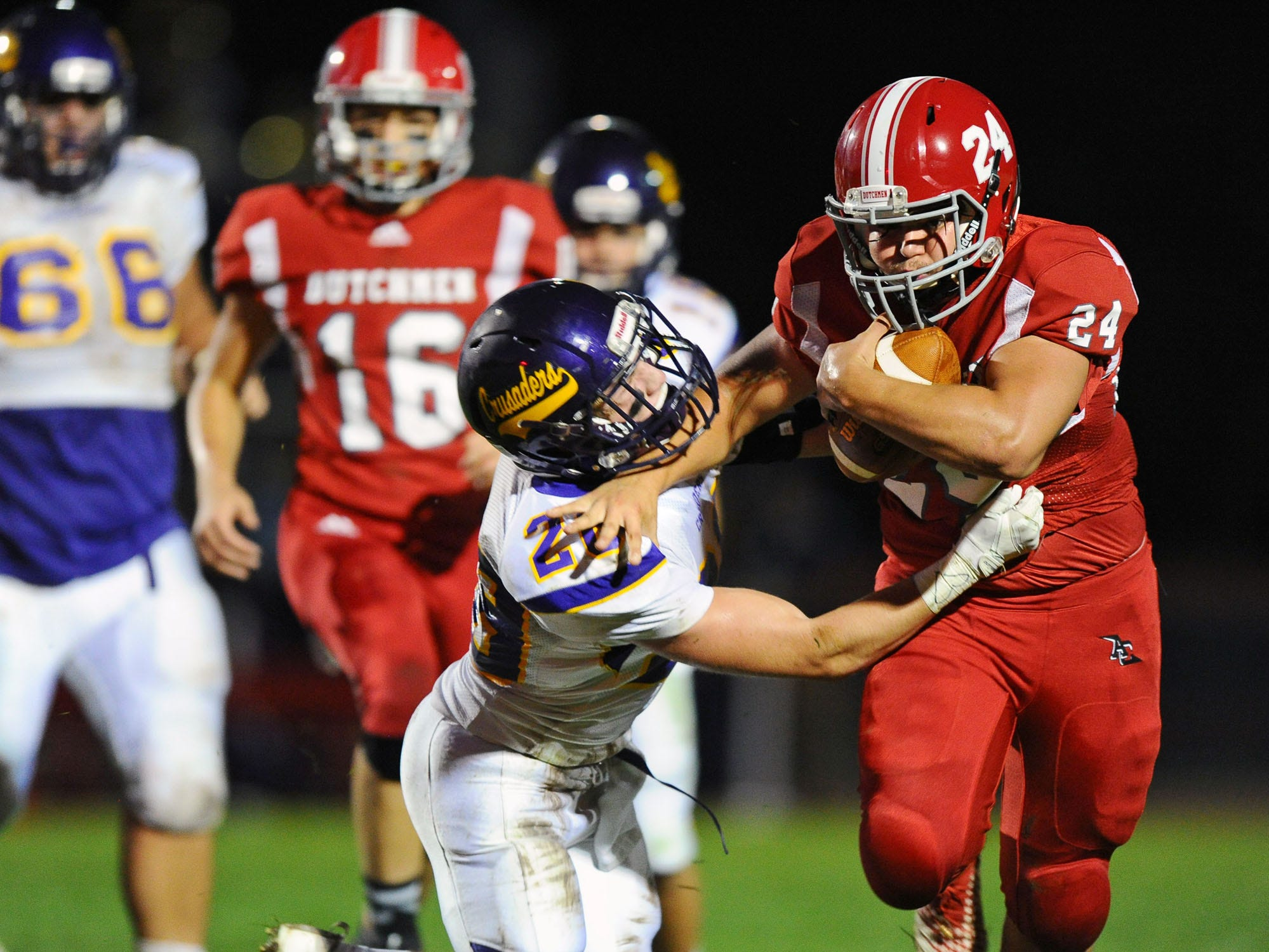 Annville-Cleona RB Caleb Turner (24) tries to get around Luke Miller (28) of Lancaster Catholic during  Friday night's game.