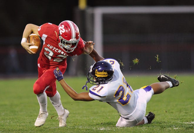 Annville Cleona's Tyler Long(22) picks up a first down on this 26-yard play as he gets around Lancaster Catholic's Nevin Roman (21) during the first quarter of Friday night's game against Lancaster Catholic.