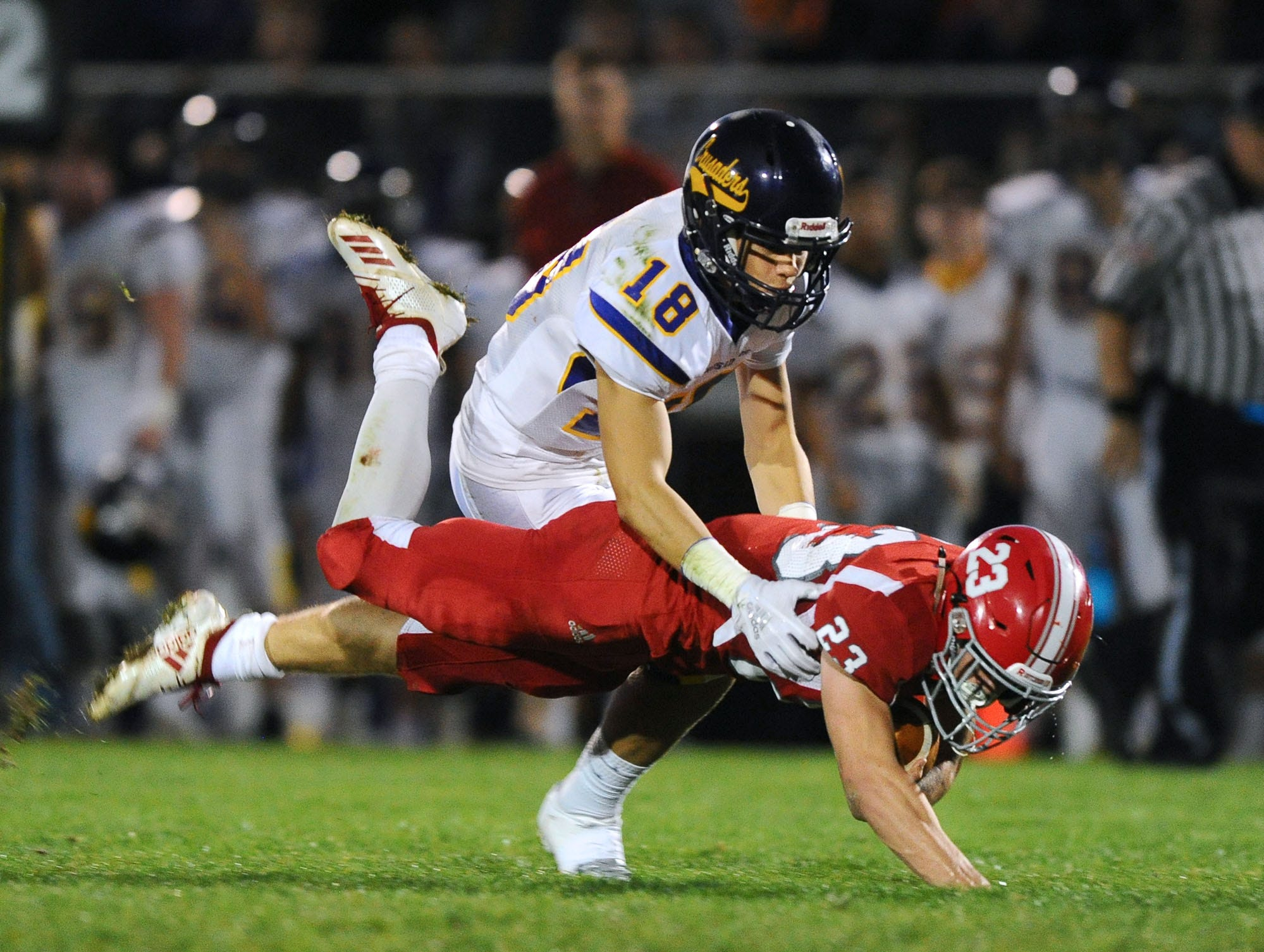 Annville Cleona's Evan Heilman (23) picks up a 1st.down as he is stopped by Lancaster Catholic's Luke Wetherhold (18) during the first quarter of Friday night's game against Lancaster Catholic.