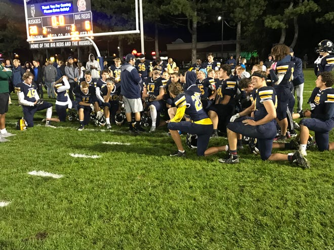 The Port Huron Northern football team listens to head coach Larry Roelens following Friday's victory.