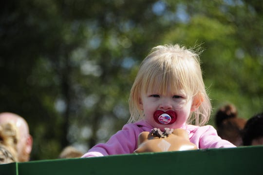 A young girl rides on a hay wagon at Scarecrow Saturday, Sept. 29, 2018 in Fort Gratiot.