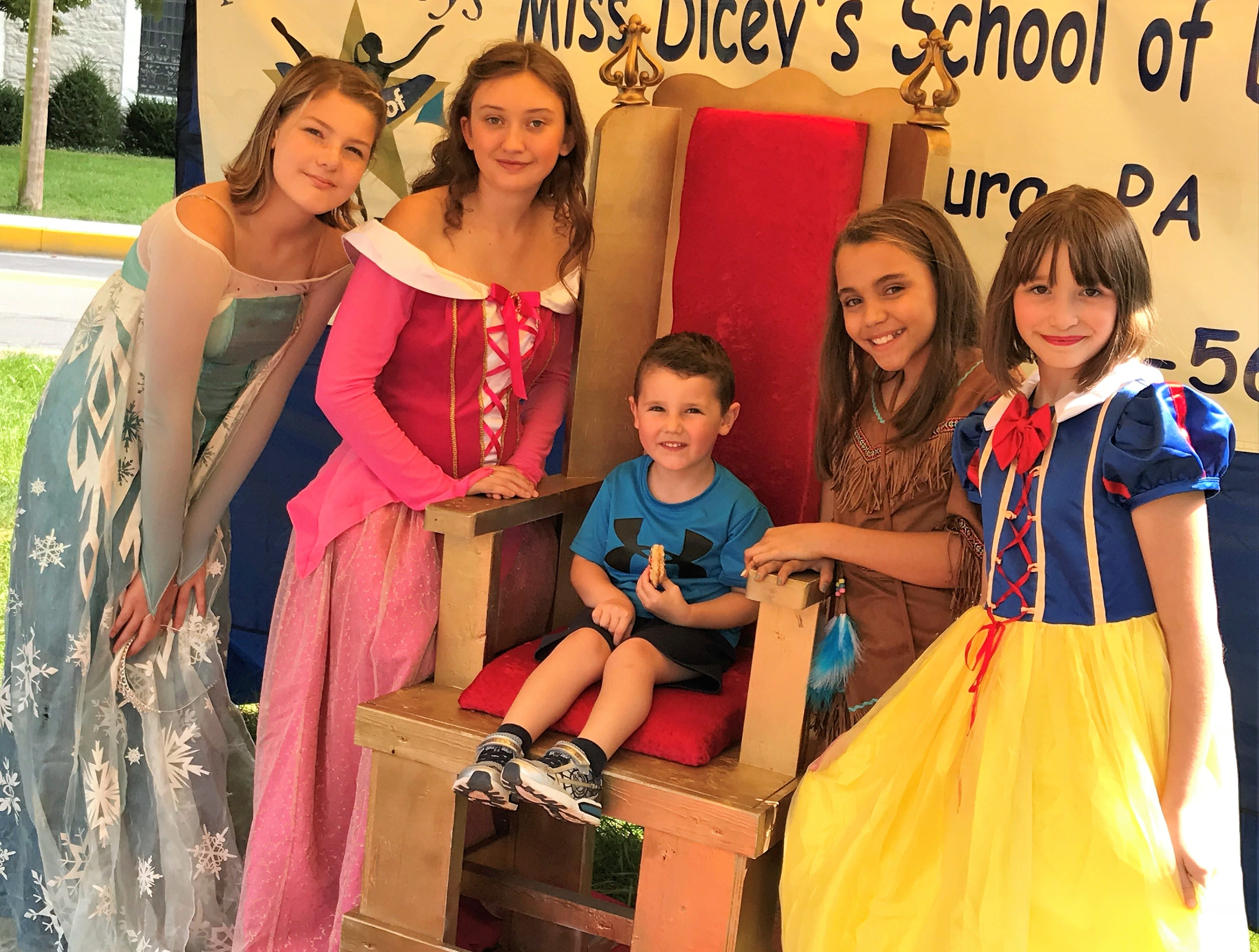 """Vincent Kiska, Greencastle, takes a photo with the """"Disney princesses"""" from Miss Dicey's School of Dance, Mercersburg,  on Saturday, Sept. 29, 2018, at Mercersburg Townfest."""