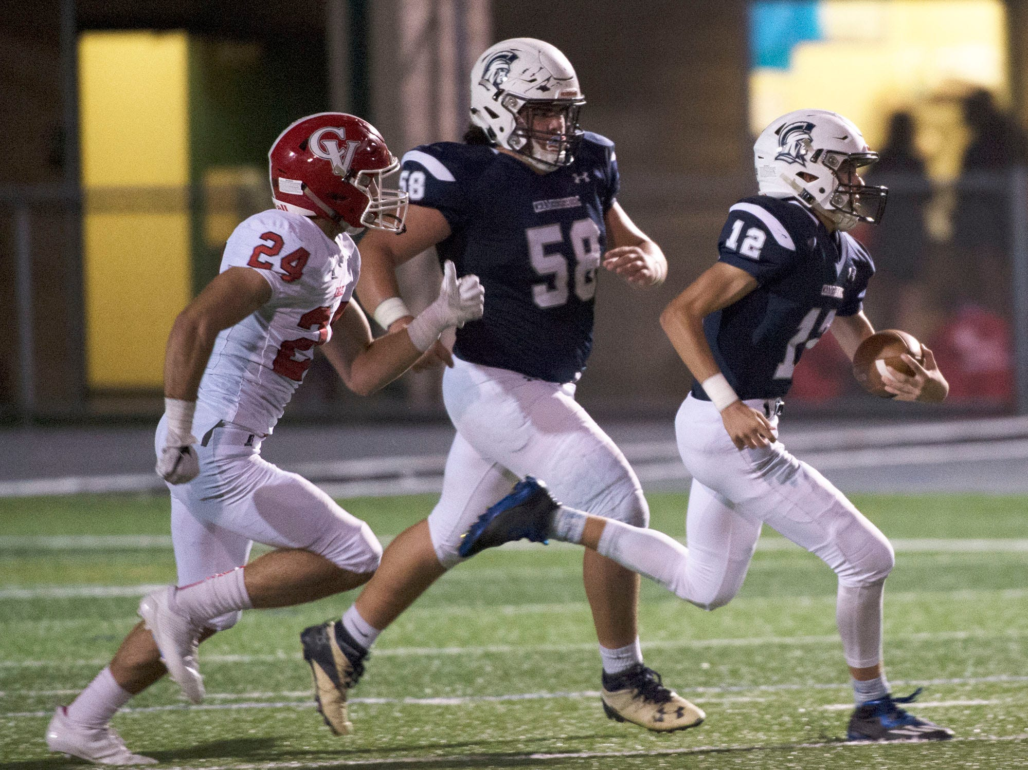 Chambersburg QB Brady Stumbaugh breaks away for a long run as teammate Tucker Karn (58) follows the play. . Chambersburg Trojans are 5-1 after a homecoming victory over Cumberland Valley 28-14 in PIAA football on Friday, Sept. 28, 2018.