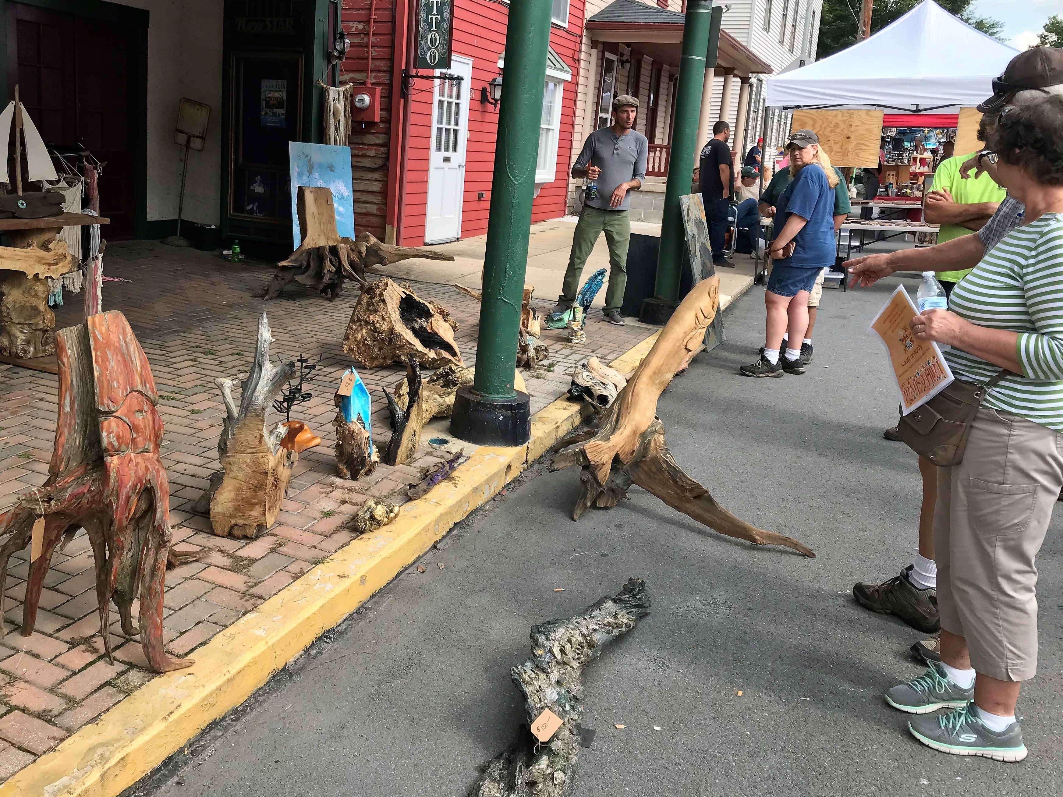 People take a look at pieces of art made from fallen branches and other wood  on Saturday, Sept. 29, 2018, at Mercersburg Townfest.