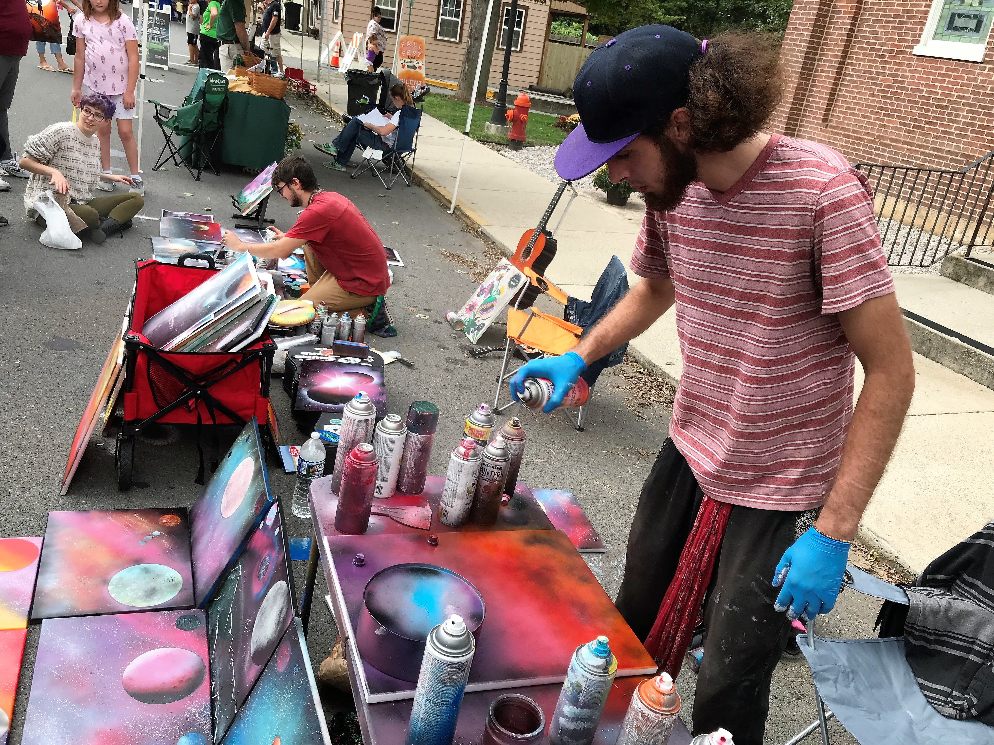 Ace Johnson and Bailey Appleby create and sell spraypaint art on Saturday, Sept. 29, 2018, at Mercersburg Townfest.