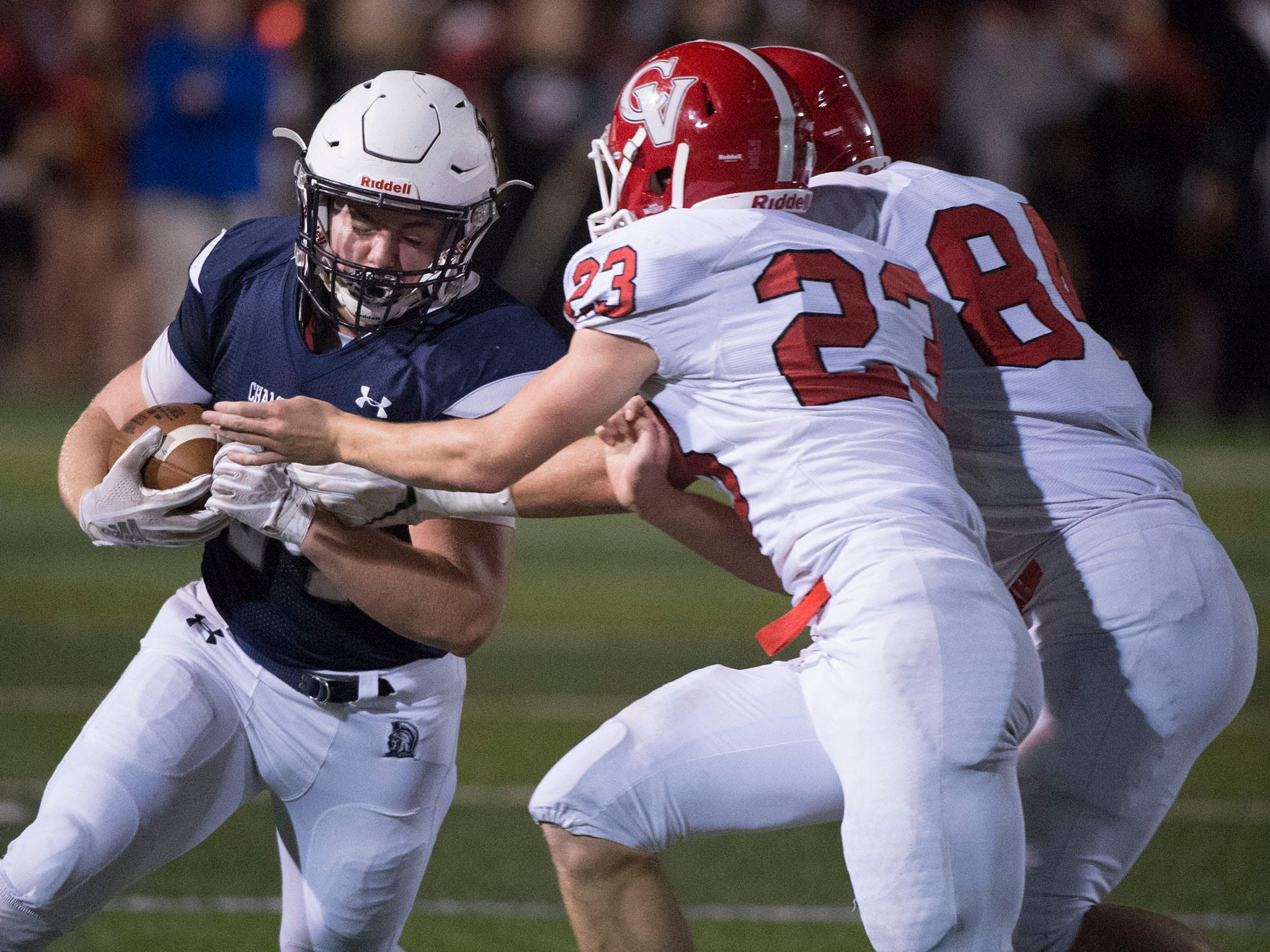 Andrew Shetter, left, of Chambersburg runs the ball as Maximos Dell'anno (23) and Stone Huffman defend. Chambersburg Trojans are 5-1 after a homecoming victory over Cumberland Valley 28-14 in PIAA football on Friday, Sept. 28, 2018.