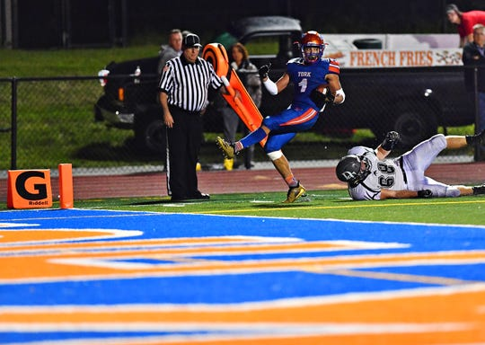 York High's Dayjure Stewart, left, scores a touchdown as Dallastown's Noah Strine falls behind during football action at Smalls Athletic Field in York City, Friday, Sept. 28, 2018. York High would win the game 68-35. Dawn J. Sagert photo