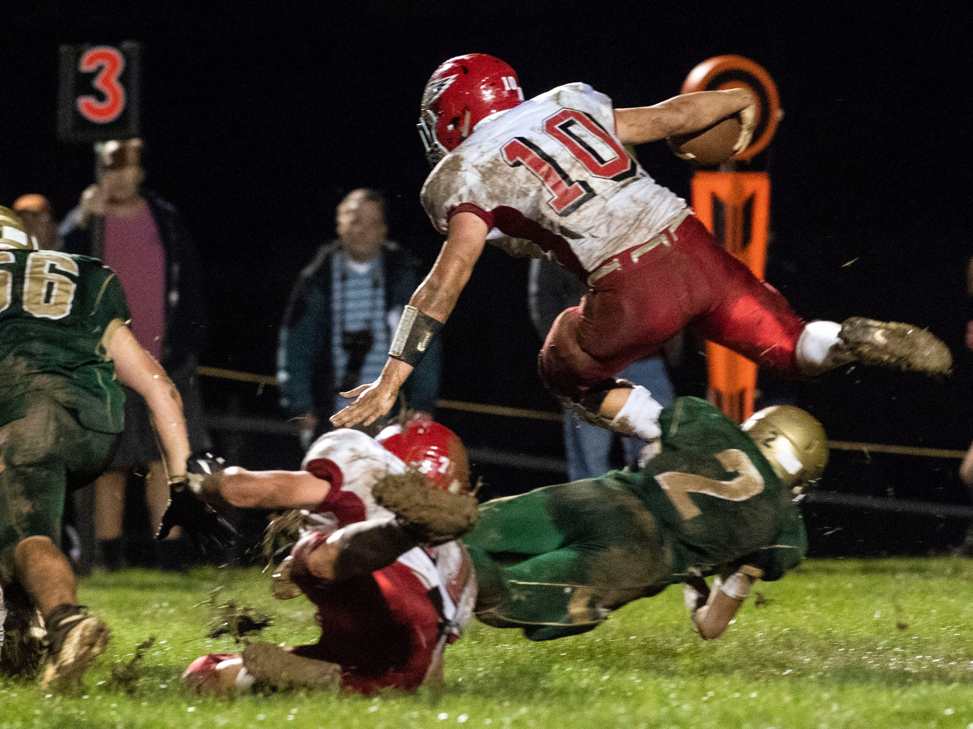 Bermudian quarterback Chase Dull (10) gets tackled mid jump by York Catholic's Massimo Antolick (2) during a Division III football game on September 28, 2018. York Catholic (6-0) beat the Bermudian Springs Eagles (4-2) 10-7, during the Fighting Irish's homecoming.