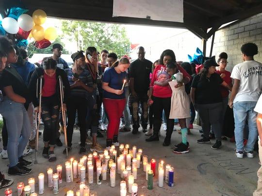 Kecia Hill hugs a girl during a vigil for her son, Dezmen Jones, on Friday night. Dezmen, 15, was fatally shot in York on Wednesday night.