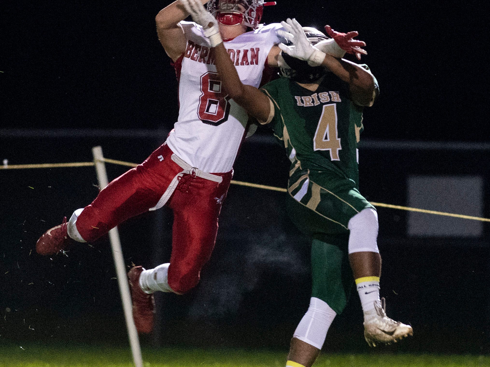 Bermudian Springs' Chase McMillan (8) and York Catholic's Tyrese Murray (4) go up for a pass from Eagles' quarterback Chase Dull during a Division III football game on September 28, 2018. York Catholic (6-0) beat the Bermudian Springs Eagles (4-2) 10-7, during the Fighting Irish's homecoming.