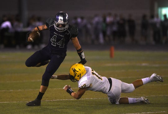 Damonte Ranch's Derrick Knoblock (44) gets past Bishop Manogue's Preston Helu (17) during their football game in Reno on Sept. 28, 2018.
