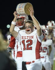 Hilton's Ryan Butts hoists the Cider Jug after Hilton's 28-15 win over Brockport on Sept. 28, 2018. Adding an eighth game to the Section V regular-season schedule could help preserve some rivalry games.