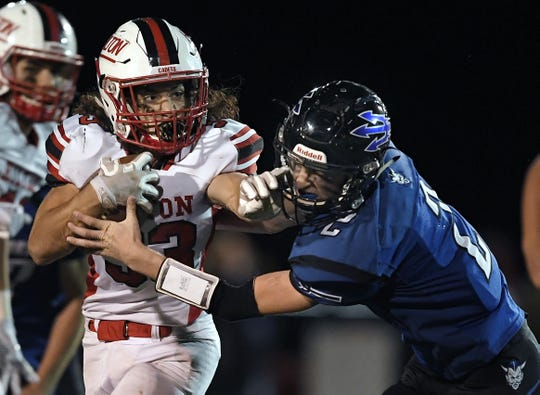 Hilton's Nick Romano, left, stiff arms Brockport's Kyle Palka during the Cadets' 28-15 win on Friday night. Romano carried 35 times for 249 yards and four touchdowns.