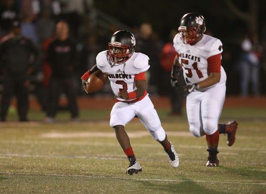 Wilson quarterback Deon Edwards looks for yards.