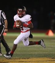 Wilson quarterback Deon Edwards rolls to his right.