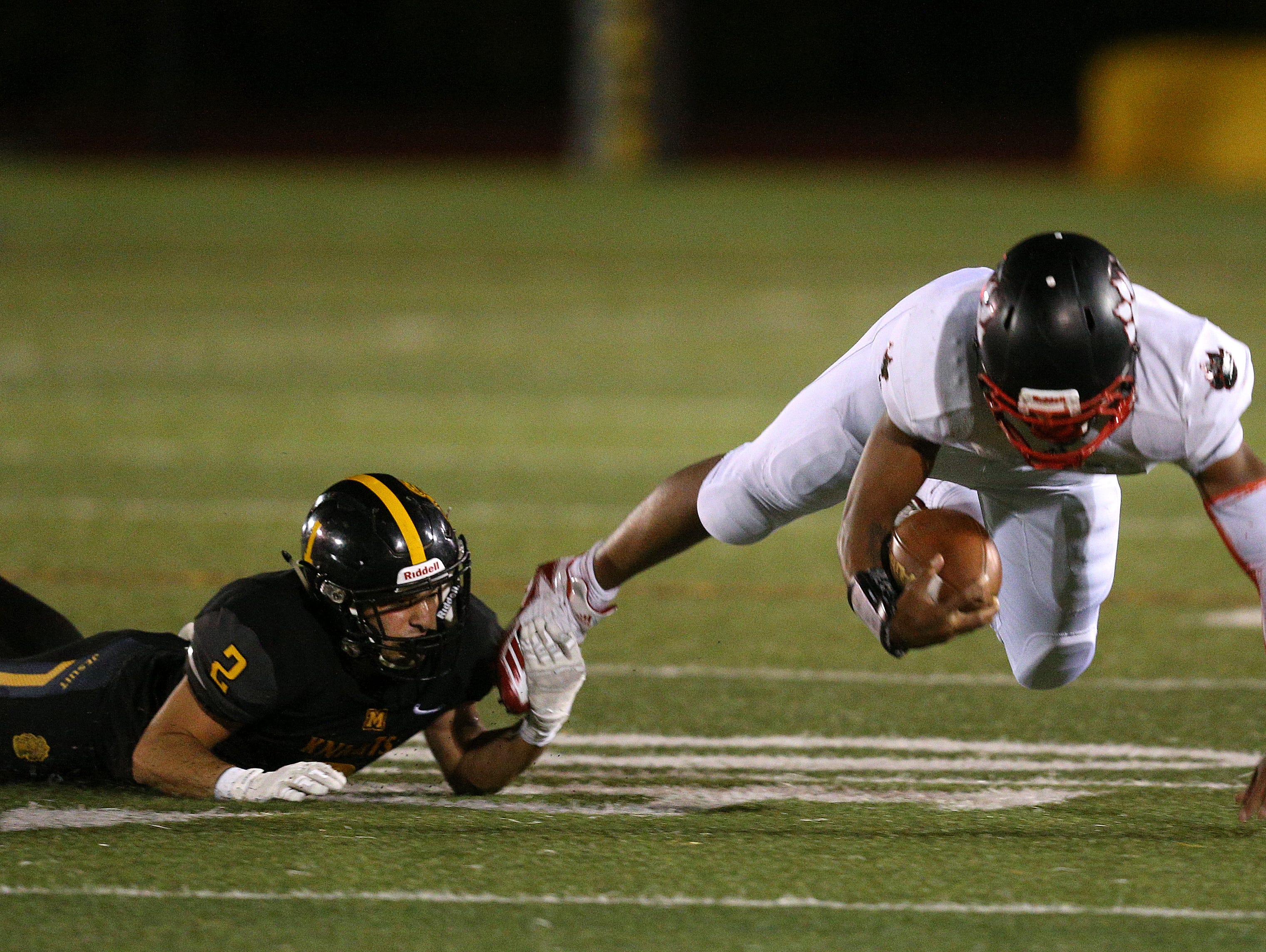 McQuaid's Josh Hill makes a shoestring tackle on Wilson's Desi Floyd Jr.  Floyd rushed for 348 yards and 2 touchdowns.