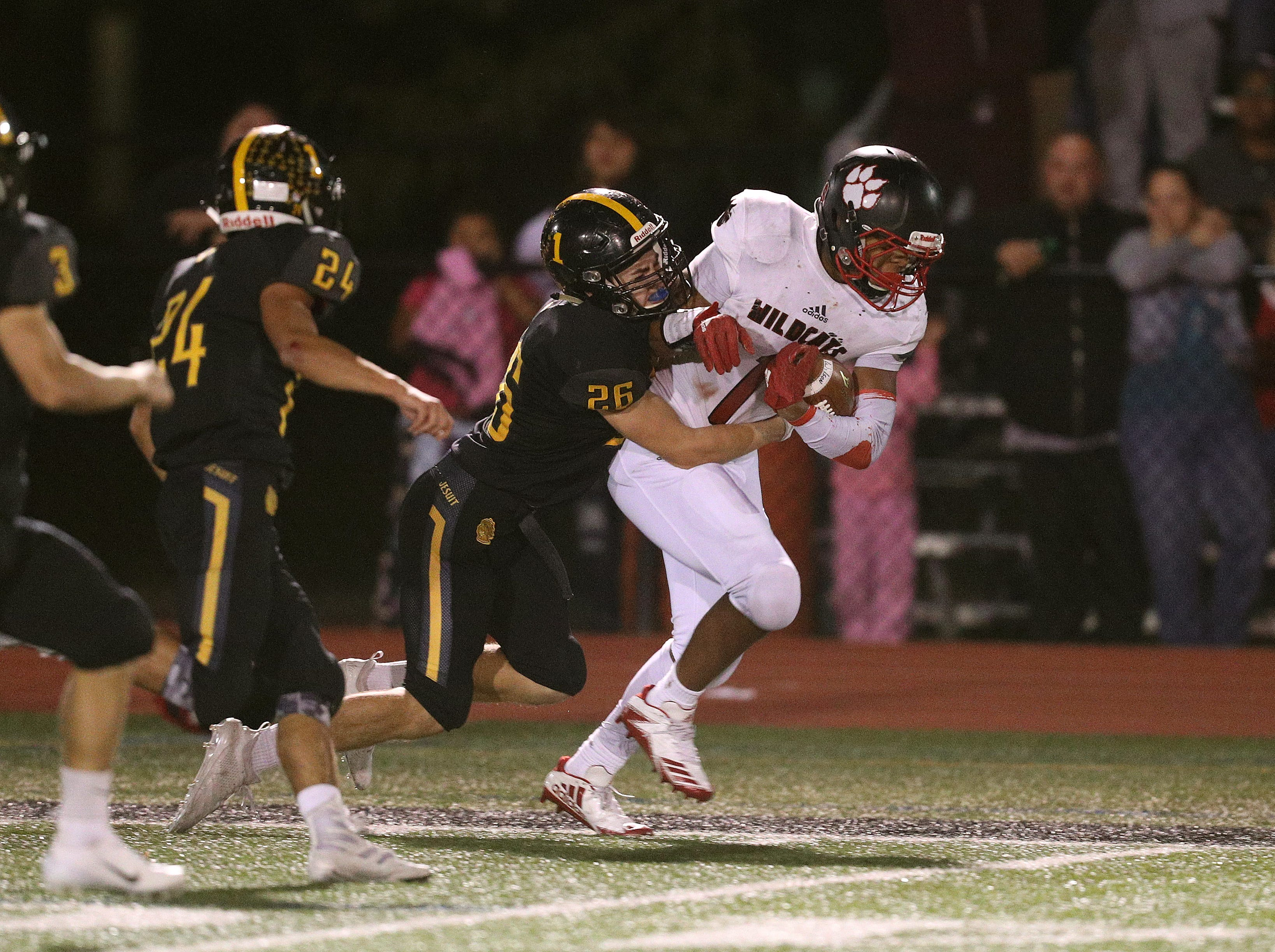 Wilson running back Desi Floyd Jr. fights through the tackle of McQuaid's Casey Howlett for extra yards.