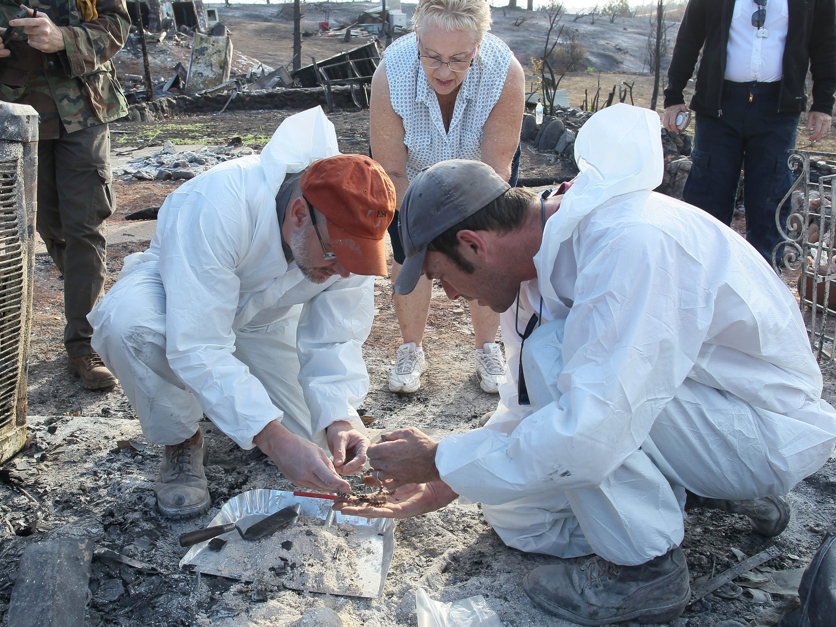 Archaeologists Mike Newland, left, and Alex Degeorgey recover cremains of Bonnie Martin's late husband's ex-wife at the burned-out home in Keswick.