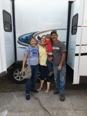 Peggy Niswander, left, Conference President of St. VIncent de Paul Society's Redding Conference, stands with Angela and Chris Foster and their young son, Kayden. The Redding family received a trailer that had housed wildfire victims in Santa Rosa.