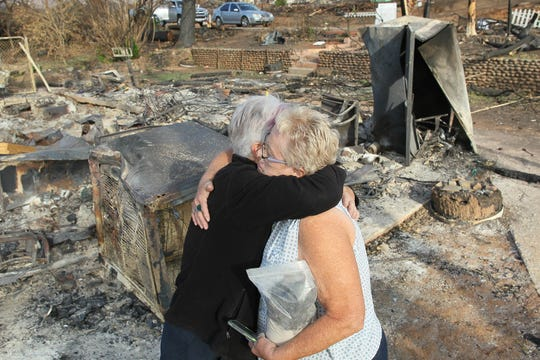 Lynne Engelbert, left, gives Bonnie Martin a hug after cremains were recovered at her burned-down home in Keswick on Saturday.