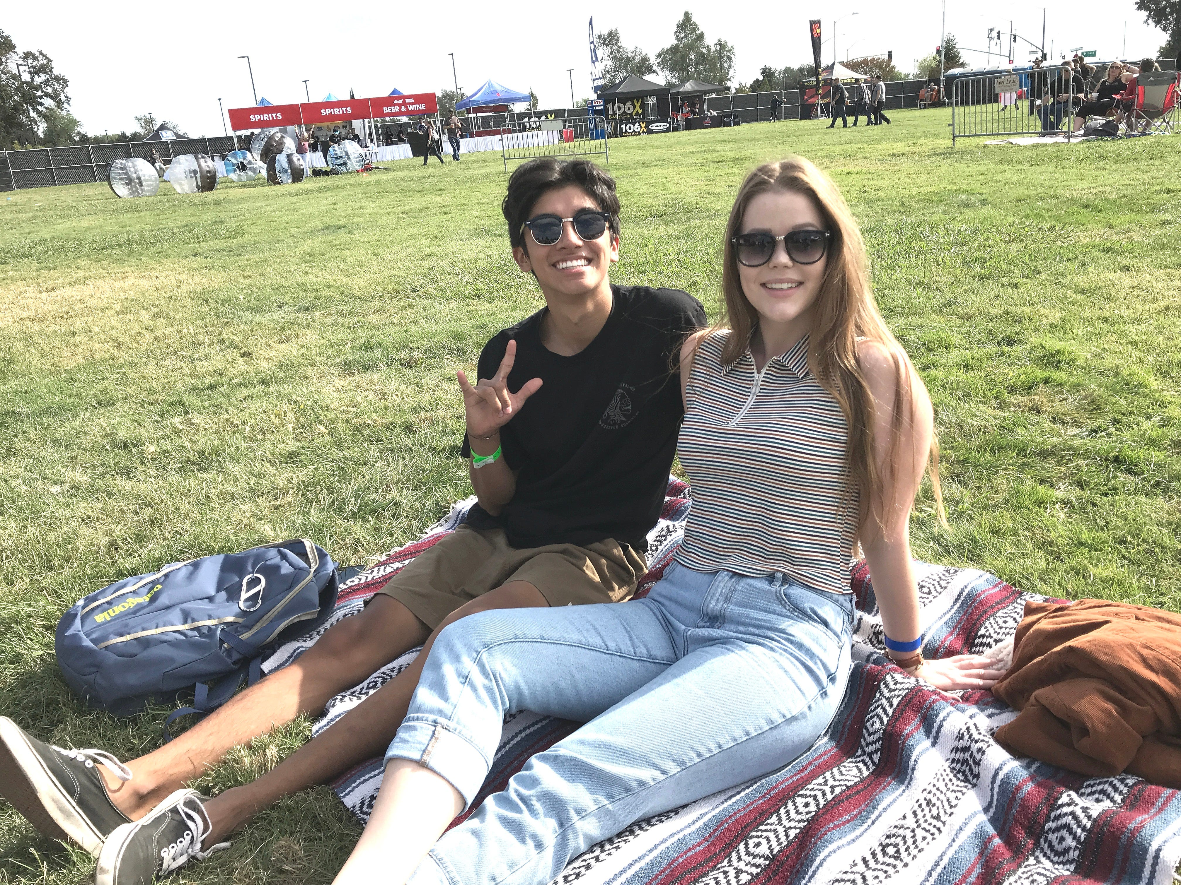 Awolnation fans Julian Christie, left, and Erin Caldwell sit on the Redding Civic Auditorium lawn Saturday afternoon before the start of the Redd Sun music festival.