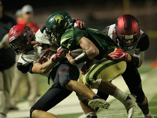Foothill's Caleb Rowe (32) and Brandon Merryman make a stop on Red Bluff's Blake Tweedt (24) in the second quarter on Friday, Sept. 28.  (Hung T. Vu/Special to the Record Searchlight)