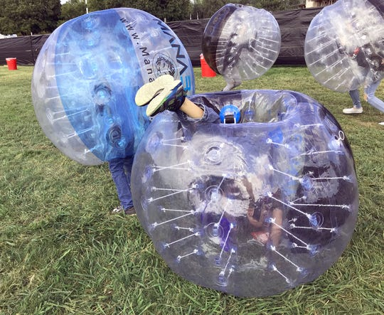 Brady Stratton, 6, of Redding rolls upside-down in a bubble ball Saturday afternoon before the start of the Redd Sun music festival at the Redding Civic Auditorium.