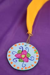 A medal painted by a child at the Salem Dream Center for the Mad Hatter Dash, a 5K fun run benefitting the Salem Dream Center, at Wallace Marine Park in West Salem on Saturday, Sept. 29, 2018.