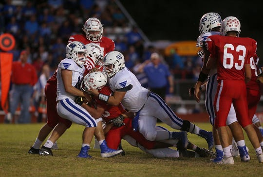 Winters High School's Slater Lindley (11) and Omar Martinez (50) bring down a Christoval runner during Friday's game in Christoval, Sept. 28, 2018.