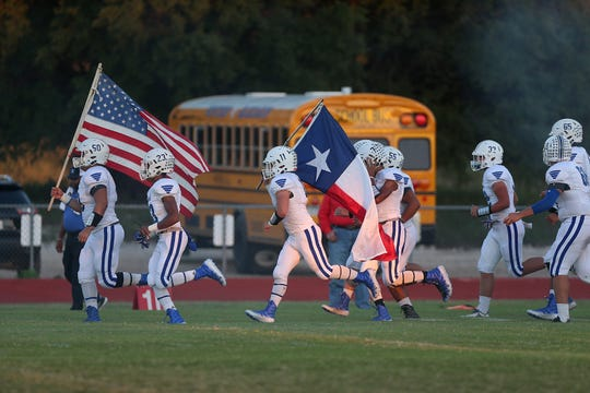 Winters players carry flags as they run onto the field before their game with Christoval on Sept. 28, 2018.