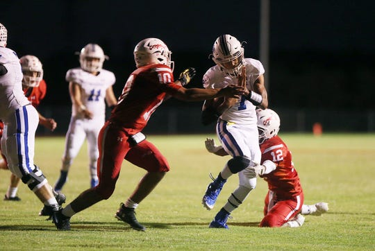 Winters' Jovan Young (#7) is brought down by Christoval's Brayden Wilcox (#10) and Apiatan Salinas (#12) during Friday night's game in Christoval, Sept. 28, 2018.