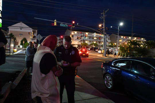 Corporal Jeff Johns takes information from a man dressed as a hot dog on Friday, Sept 28, 2018. Popular car show H2Oi  was traditionally held nearby and though it has now moved to Atlantic City attendees continue to flock to Ocean City.