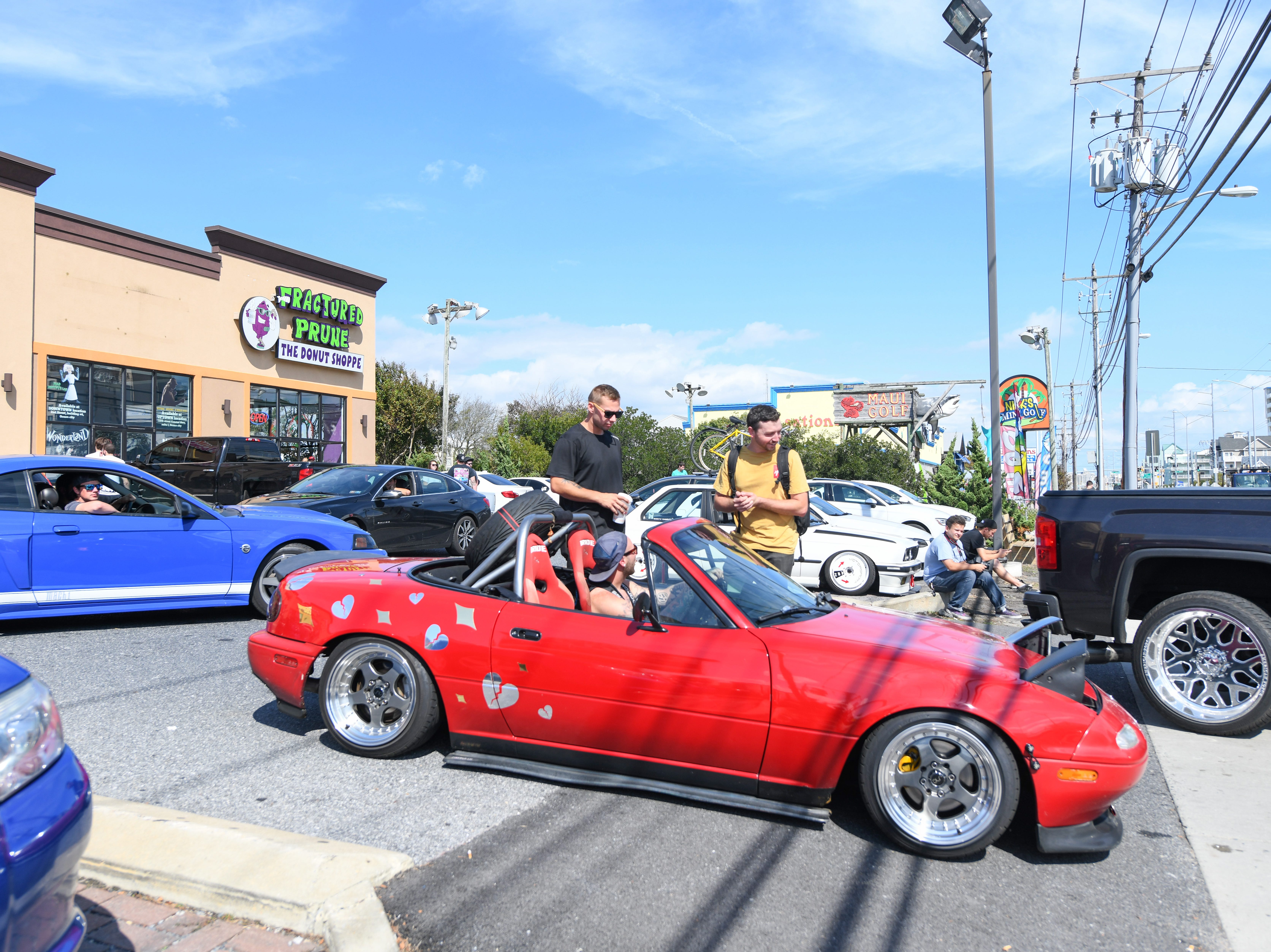 A crowd gathers starts to gather at an Ocean City parking lot on Saturday, Sept 29, 2018. Streets in the area were full of crowds and cars for the unofficial H2Oi weekend, despite the fact that the car show has moved to Atlantic City.