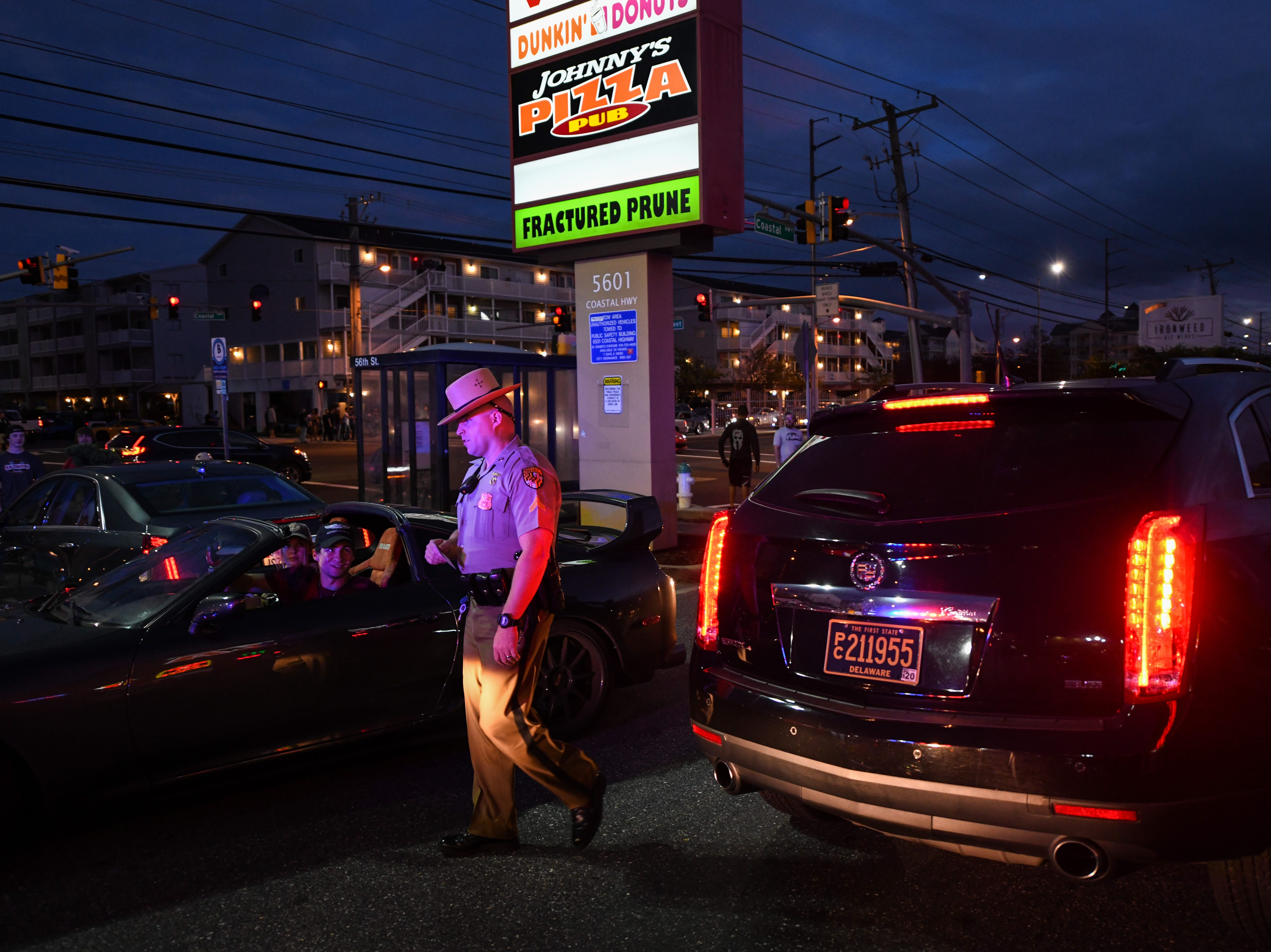 An officer speaks with a car pulled into a parking lot on Friday, Sept 28, 2018. Popular car show H2Oi  was traditionally held nearby and though it has now moved to Atlantic City attendees continue to flock to Ocean City.